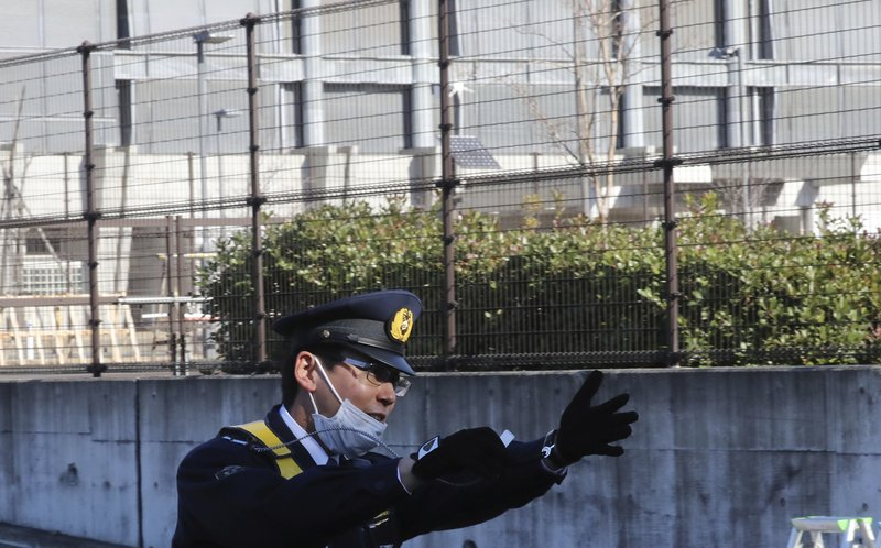 A police officer gestures in front of the gate of Tokyo Detention Center, where former Nissan chairman Carlos Ghosn and another former executive Greg Kelly, are being detained, in Tokyo Tuesday, Dec. (AP Photo/Eugene Hoshiko)