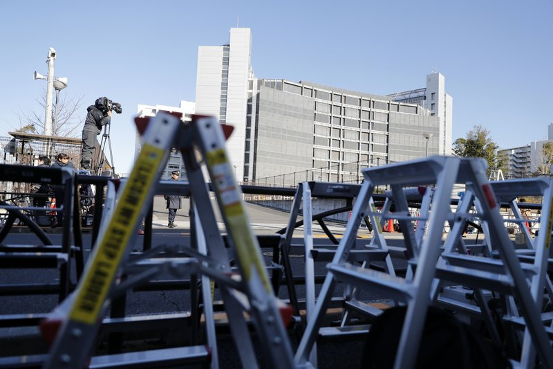 Step ladders of cameramen and photographers are placed in front of the gate of Tokyo Detention Center, where former Nissan chairman Carlos Ghosn and another former executive Greg Kelly, are being detained on suspicion of falsifying financial reports, in Tokyo Tuesday, Dec. (AP Photo/Eugene Hoshiko)