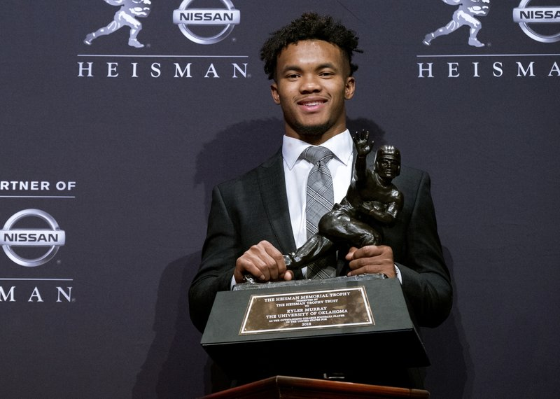 FILE - In this Dec. 8, 2018, file photo, Oklahoma quarterback Kyler Murray holds the Heisman Trophy after winning the award in New York. (205.72) of Oklahoma and Alabama's Tua Tagovailoa (202.30) are on pace to break the record for passer efficiency rating set by former Sooners quarterback Baker Mayfield (198.92) last season. (AP Photo/Craig Ruttle, File)