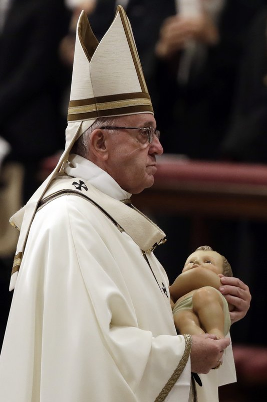 Pope Francis holds a statue of baby Jesus as he leaves at the end of the Christmas Eve Mass in St. Peter's Basilica at the Vatican, Monday, Dec. (AP Photo/Alessandra Tarantino)