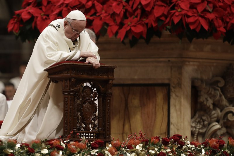 Pope Francis kneels on the altar as he celebrates the Christmas Eve Mass in St. Peter's Basilica at the Vatican, Monday, Dec. (AP Photo/Alessandra Tarantino)