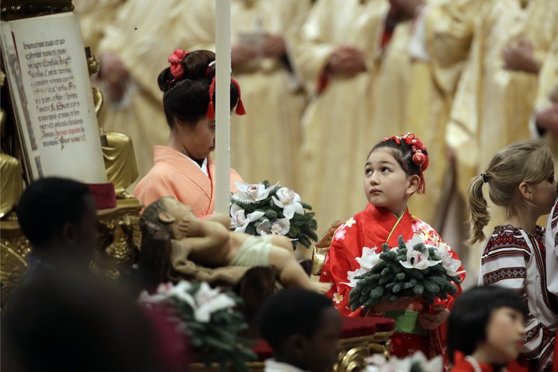 Children walk past a statue of baby Jesus at the end of the Christmas Eve Mass celebrated by Pope Francis in St. (AP Photo/Alessandra Tarantino)