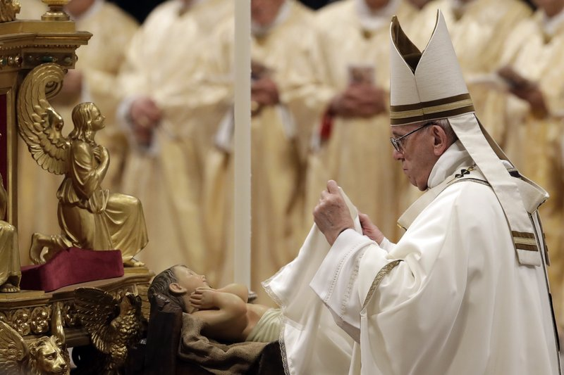 Pope Francis unveils a statue of Baby Jesus as he celebrates the Christmas Eve Mass in St. Peter's Basilica at the Vatican, Monday, Dec. (AP Photo/Alessandra Tarantino)