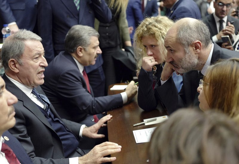 Turkey's Defense Minister and former top army commander Hulusi Akar, left, speaks about Turkish military's possible operation in Syria at the parliament in Ankara, Tuesday, Dec. (AP Photo/Burhan Ozbilici)