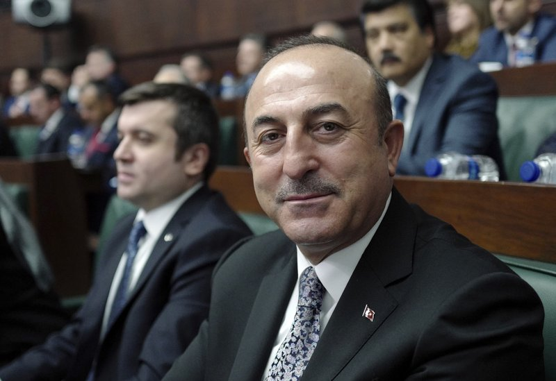 Turkey's Foreign Minister Mevlut Cavusoglu speaks to a journalist at the parliament in Ankara, Tuesday, Dec. (AP Photo/Burhan Ozbilici)