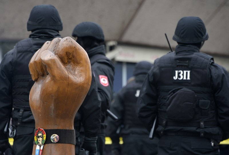 Bosnian Serb police secure an area at the spot with the symbol of a raised hand and a picture of the late David Dragicevic on it, in Bosnian town of Banja Luka, northwest of Sarajevo, Bosnia, Tuesday, Dec. (AP Photo/Radivoje Pavicic)