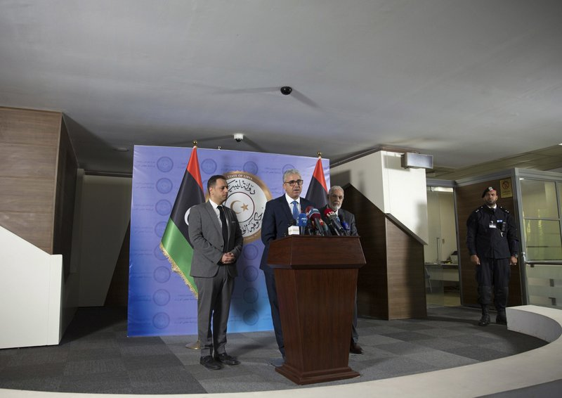 Libyan Foreign Minister Mohamed Siala, right, Interior Minister Fathi Bash Agha, center and Spokesperson for the President of the Presidency Council Mohamed el-Sallak give a press conference shortly after an attack on the foreign ministry building, in Tripoli, Libya, Tuesday, Dec, 25, 2018. (AP Photo/Mohamed Ben Khalifa)