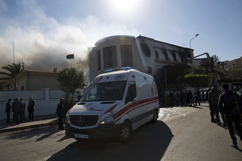 An ambulance carries injured as smoke rises following a deadly attack on the foreign ministry building, in Tripoli, Libya, Tuesday, Dec, 25, 2018. (AP Photo/Mohamed Ben Khalifa)