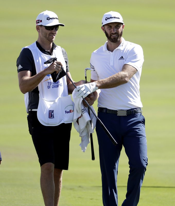 FILE - In this Jan. 4, 2017, file photo, Dustin Johnson, right, exchanges clubs with his caddy, brother Austin Johnson, on the 18th green during the pro-am prior to the Tournament of Champions golf event, at Kapalua Plantation Course in Kapalua, Hawaii. (AP Photo/Matt York, File)