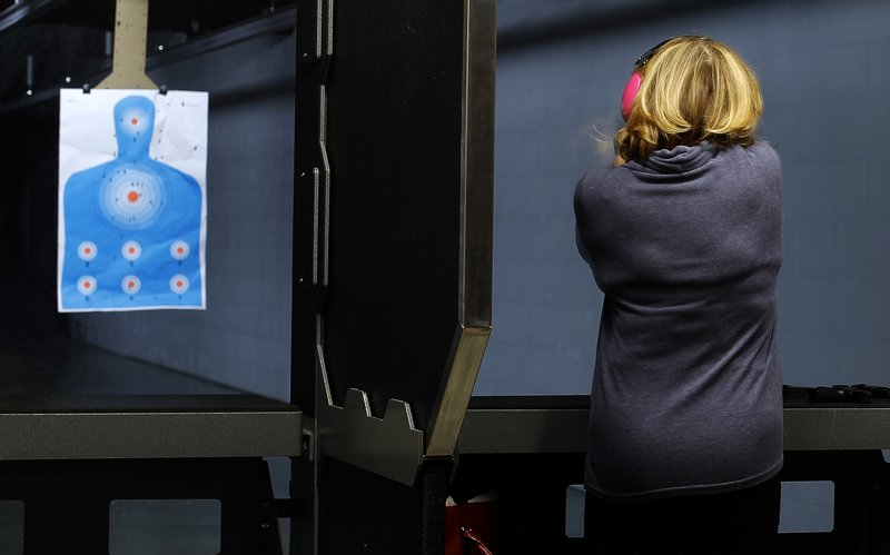 In this Dec. 21, 2018 photo, a woman takes aim at a target on the shooting range at Frontier Justice in Lee's Summit, Mo. (AP Photo/Charlie Riedel)