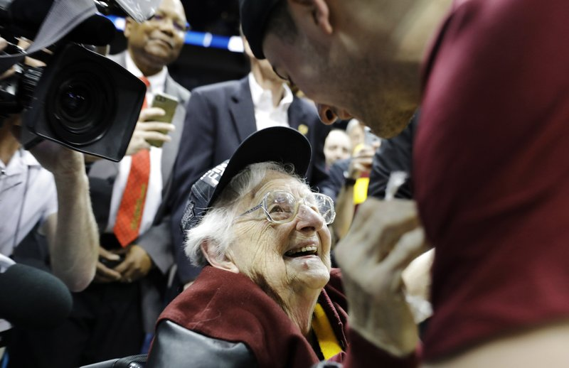 FILE - In this March 24, 2018, file photo, Loyola-Chicago basketball chaplain Sister Jean Dolores Schmidt speaks with Loyola-Chicago guard Ben Richardson after a regional final NCAA college basketball tournament game between Loyola-Chicago and Kansas State in Atlanta. (AP Photo/David Goldman, File)
