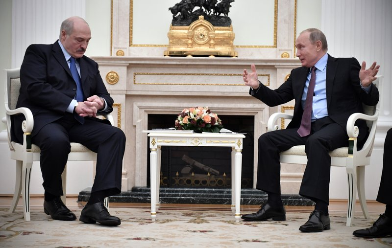 Russian President Vladimir Putin, right, gestures as he speaks to his Belarusian counterpart Alexander Lukashenko, foreground left, during their talks in the Kremlin in Moscow, Russia, Tuesday, Dec. (Alexander Nemenov/Pool Photo via AP)