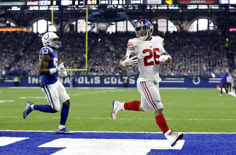 FILE - In this Dec. 23, 2018, file photo, New York Giants running back Saquon Barkley (26) runs in for a touchdown in front of Indianapolis Colts outside linebacker Darius Leonard (53) during the first half of an NFL football game in Indianapolis. (AP Photo/AJ Mast, File)