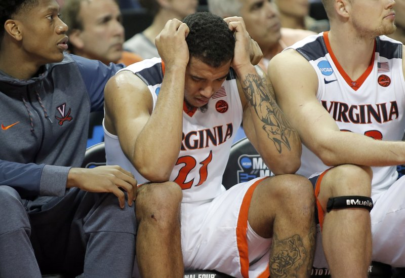 FILE - In this March 16, 2018, file photo, Virginia's Isaiah Wilkins (21) is consoled after fouling out in the second half of the team's first-round game against UMBC in the NCAA men's college basketball tournament in Charlotte, N. (AP Photo/Bob Leverone, File)
