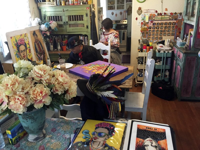 In this Thursday, April 5, 2018 photo artist Moises Salcedo (left) of Albuquerque, who goes by the name El Moises, sits amid his artwork at his home and studio in Albuquerque, N. (AP Photo/Morgan Lee)
