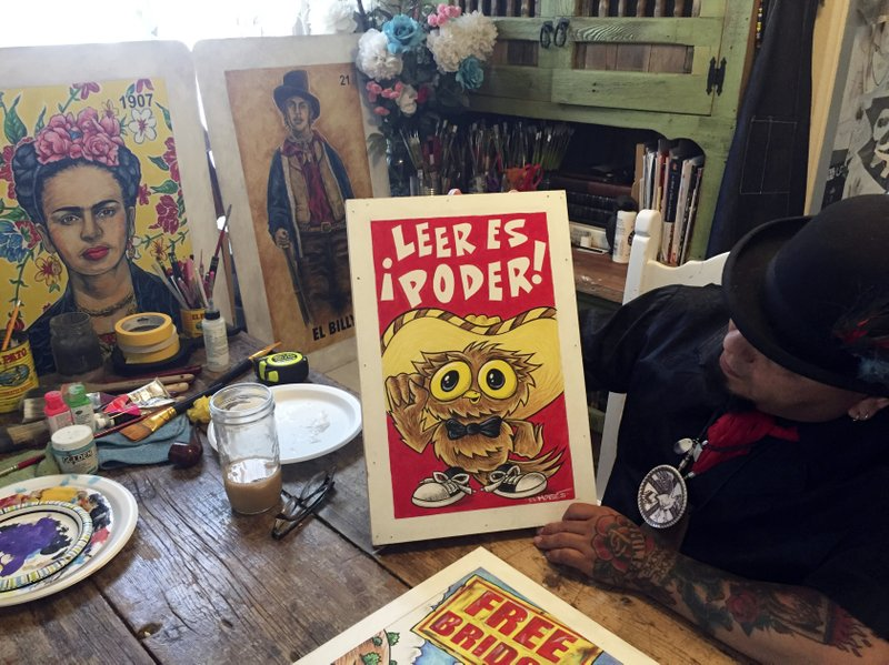 In this Thursday, April 5, 2018 photo artist Moises Salcedo of Albuquerque, who goes by the name El Moises, shows an early rendition of the lead character for the bilingual children's book