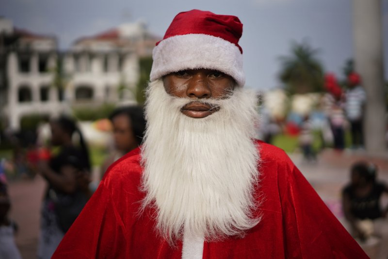 A Congolese Santa Claus waits to pose with children in Kinshasa, Congo, Tuesday Dec. 25, 2018. Traditionally Congolese dress up and take to the parks on Christmas day, this time five days before scheduled presidential and general elections. (AP Photo/Jerome Delay)