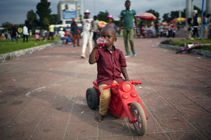 A Congolese child rides his tricycle in Kinshasa , Congo, Tuesday Dec. 25, 2018. Traditionally Congolese dress up and take to the parks on Christmas day, this time five days before scheduled presidential and general elections. (AP Photo/Jerome Delay)