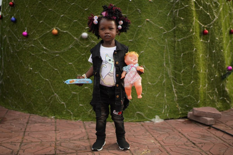 A Congolese child poses for a photograph in Kinshasa, Congo, Tuesday Dec. 25, 2018. Traditionally Congolese dress up and take to the parks on Christmas day, this time five days before scheduled presidential and general elections. (AP Photo/Jerome Delay)