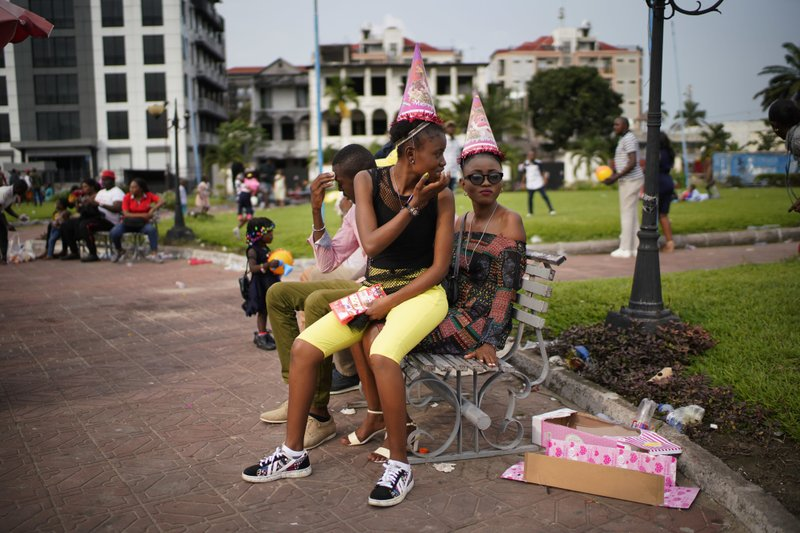 Congolese youth sit on a park bench in Kinshasa, Congo, Tuesday Dec. 25, 2018. Traditionally Congolese dress up and take to the parks on Christmas day, this time five days before scheduled presidential and general elections. (AP Photo/Jerome Delay)