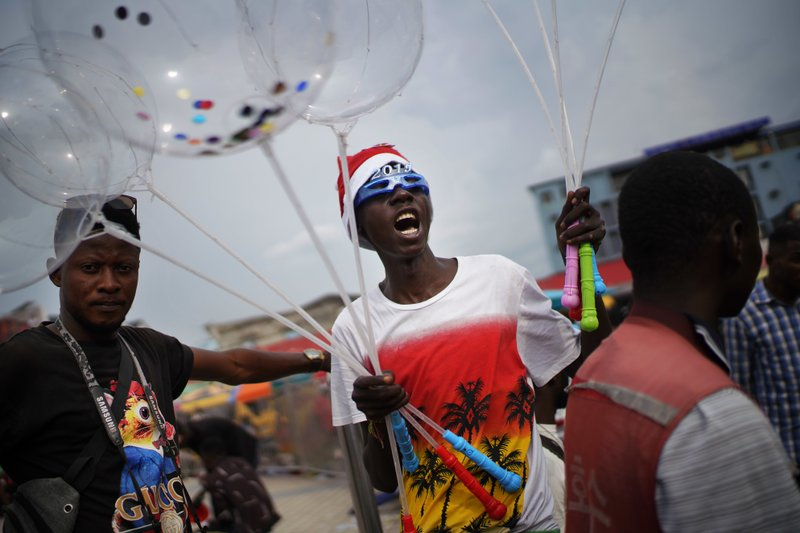 A Congolese man sells balloons in Kinshasa, Congo, Tuesday Dec. 25, 2018. Traditionally Congolese dress up and take to the parks on Christmas day, this time five days before scheduled presidential and general elections. (AP Photo/Jerome Delay)