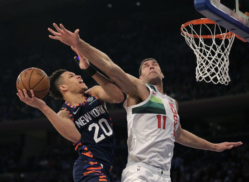 New York Knicks' Kevin Knox, left, drives to the basket past Milwaukee Bucks' Brook Lopez during the first half of the NBA basketball game, Tuesday, Dec. (AP Photo/Seth Wenig)