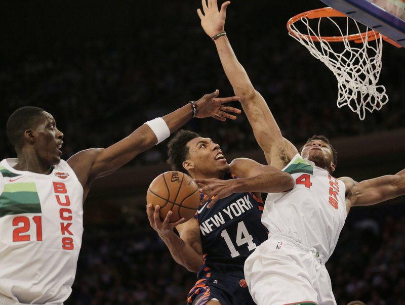 New York Knicks' Allonzo Trier (14) drives past Milwaukee Bucks defenders during the first half of the NBA basketball game, Tuesday, Dec. (AP Photo/Seth Wenig)