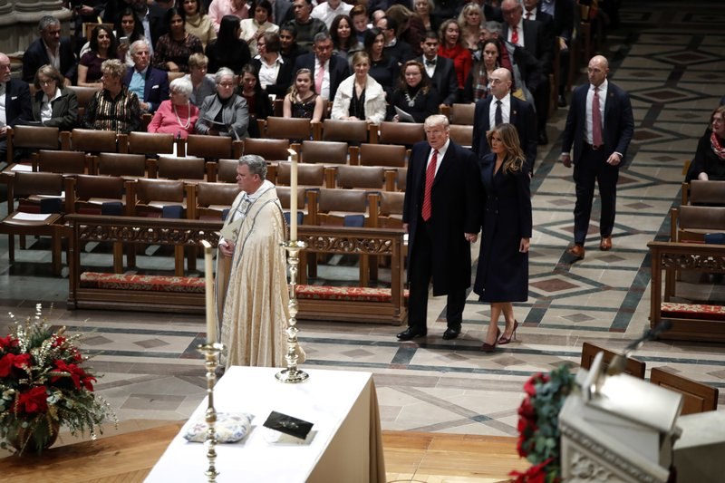 President Donald Trump and first lady Melania Trump arrive for a Christmas Eve service at the National Cathedral, Monday, Dec. (AP Photo/Jacquelyn Martin)