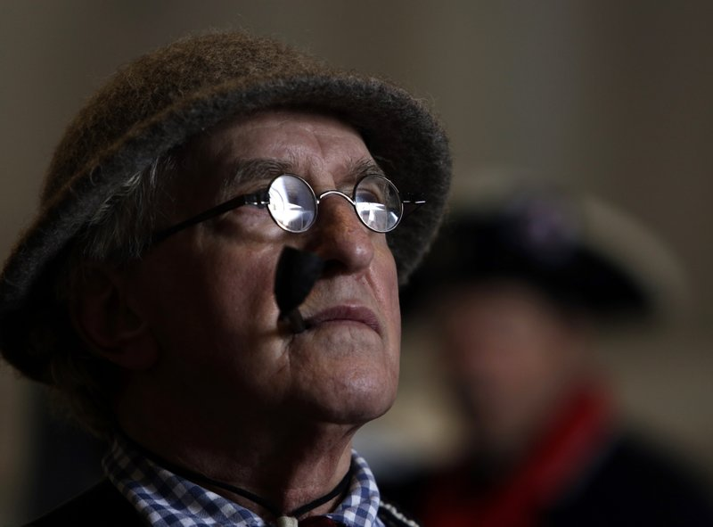 Re-enactor John Niemiec, who portrays an oarsman, listens at a gathering inside a boathouse Tuesday Dec. (AP Photo/Jacqueline Larma)