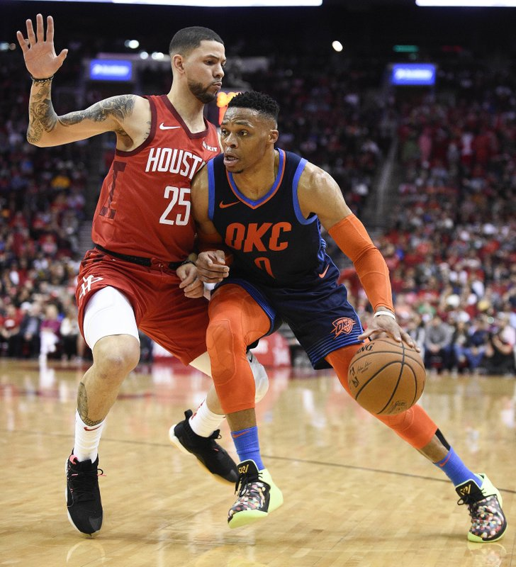 Oklahoma City Thunder guard Russell Westbrook, right, dribbles past Houston Rockets guard Austin Rivers, left, during the first half of an NBA basketball game, Tuesday, Dec. (AP Photo/Eric Christian Smith)