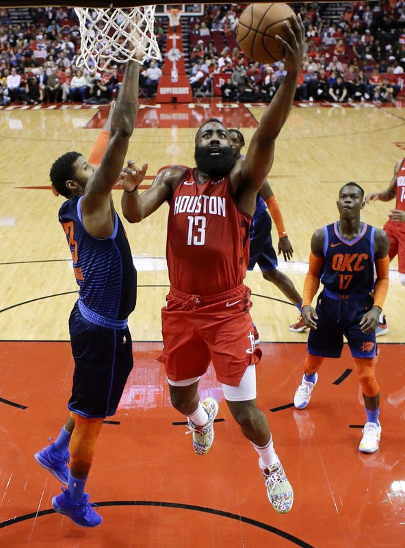 Houston Rockets guard James Harden, right, drives to the basket post Oklahoma City Thunder forward Paul George, left, during the first half of an NBA basketball game, Tuesday, Dec. (AP Photo/Eric Christian Smith)