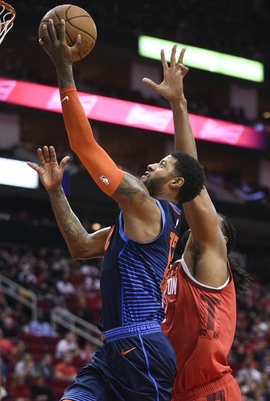Oklahoma City Thunder forward Paul George, left, drives to the basket past Houston Rockets center Nene Hilario during the first half of an NBA basketball game, Tuesday, Dec. (AP Photo/Eric Christian Smith)