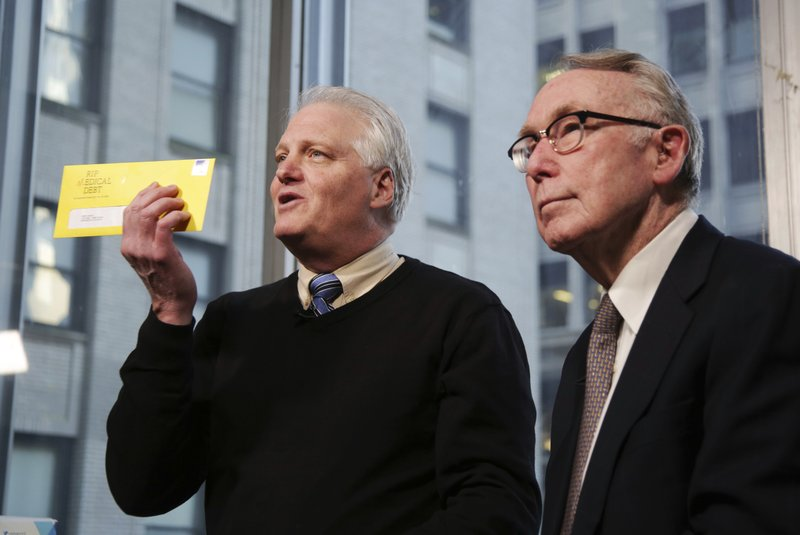 In this Dec. 19, 2018 photo, Craig Antico, left, and Jerry Ashton, co-founders of RIP Medical Debt, talks to reporters in New York. (AP Photo/Seth Wenig)