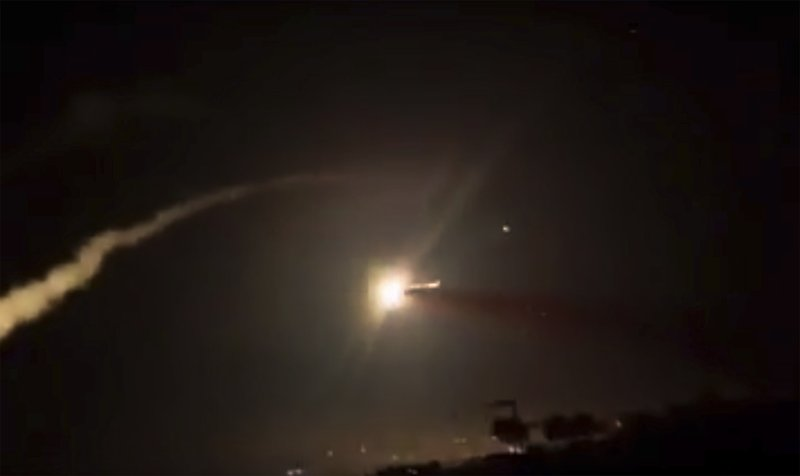 This frame grab from a video provided by the Syrian official news agency SANA shows missiles flying into the sky near Damascus, Syria, Tuesday, Dec. (SANA via AP)