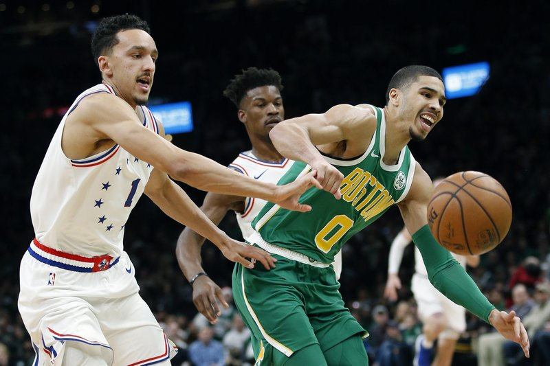 Boston Celtics' Jayson Tatum (0) and Philadelphia 76ers' Landry Shamet (1) can't come up with a loose ball during the first half of an NBA basketball game in Boston, Tuesday, Dec. (AP Photo/Michael Dwyer)