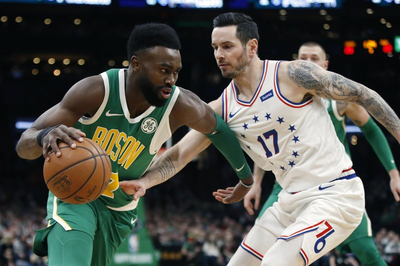 Boston Celtics' Jaylen Brown (7) is defended by Philadelphia 76ers' JJ Redick (17) during the first half of an NBA basketball game in Boston, Tuesday, Dec. (AP Photo/Michael Dwyer)