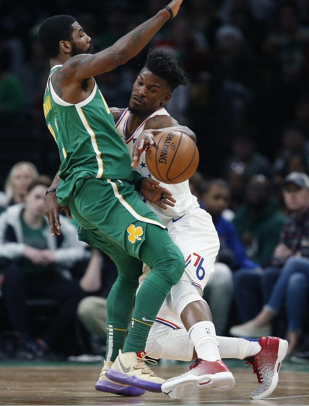 Philadelphia 76ers' Jimmy Butler, right, fouls Boston Celtics' Kyrie Irving during the first half of an NBA basketball game in Boston, Tuesday, Dec. (AP Photo/Michael Dwyer)