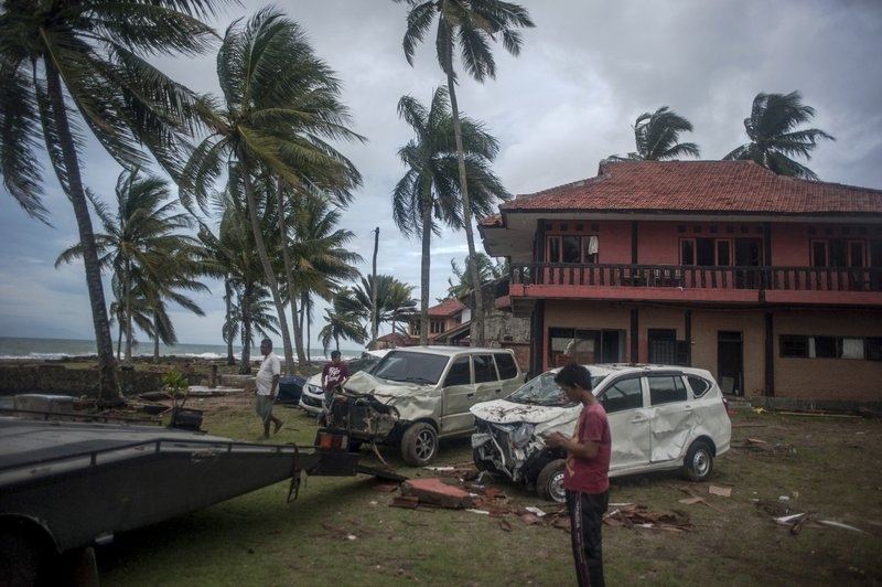 Owners reclaim their damaged cars from a resort affected by Saturday's tsunami in Carita, Indonesia, Tuesday, Dec. (AP Photo/Fauzy Chaniago)