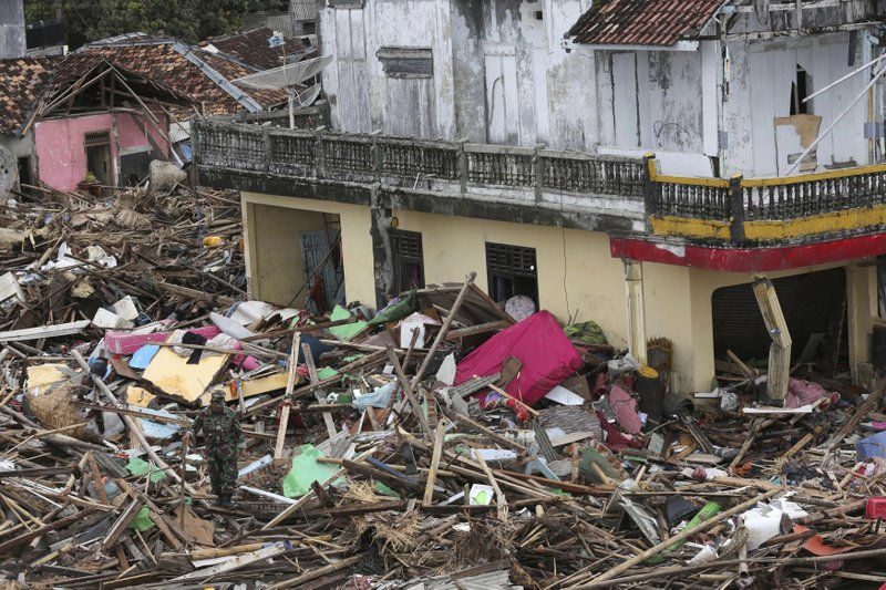 An Indonesian soldier inspects the damage at a tsunami-ravaged village in Sumur, Indonesia, Tuesday, Dec. (AP Photo/Tatan Syuflana)