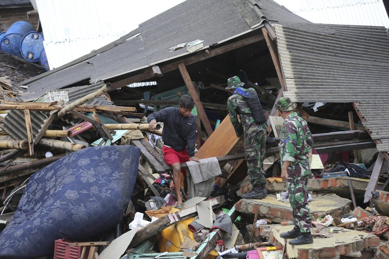 Indonesian soldiers and people clean up the debris following the tsunami in Sumur, Indonesia, Tuesday, Dec. (AP Photo/Tatan Syuflana)