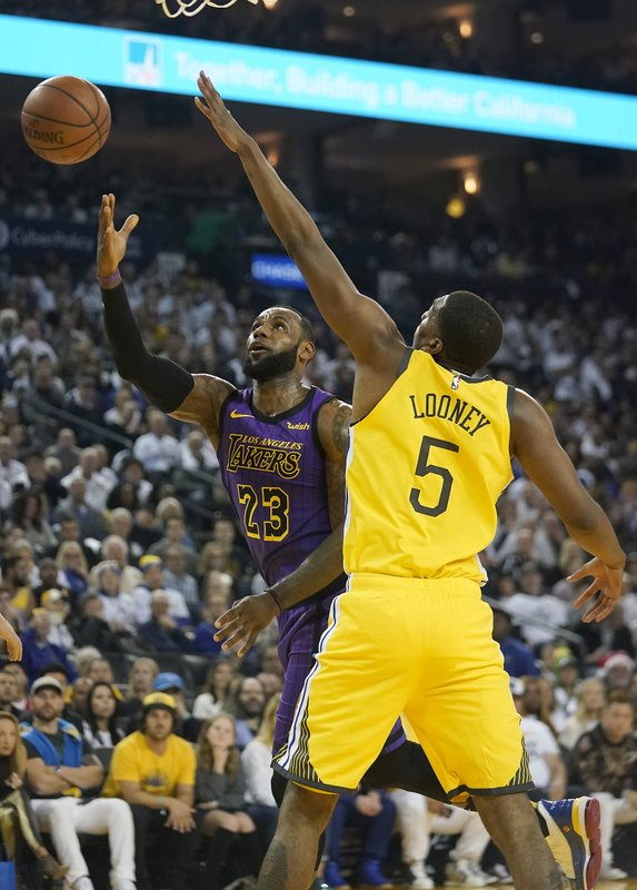 Los Angeles Lakers forward LeBron James (23) drives to the basket against Golden State Warriors forward Kevon Looney (5) during the first half of an NBA basketball game Tuesday, Dec. (AP Photo/Tony Avelar)