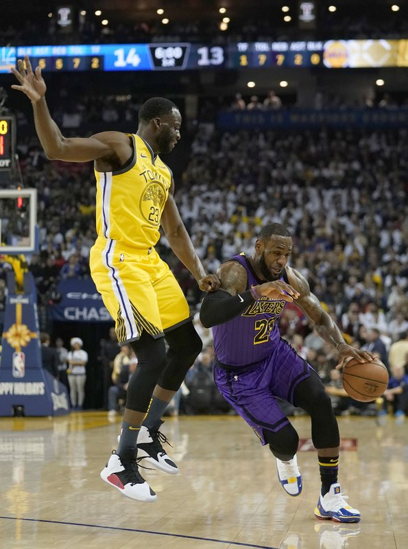 Golden State Warriors forward Draymond Green (23) fouls Los Angeles Lakers forward LeBron James (23) during the first half of an NBA basketball game Tuesday, Dec. (AP Photo/Tony Avelar)
