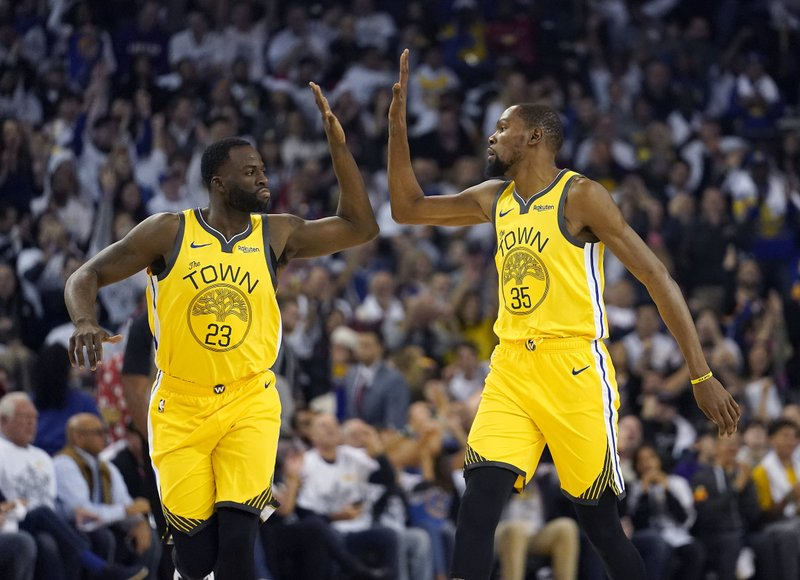 Golden State Warriors forward Draymond Green (23) high-fives Kevin Durant (35) after the latter's 3-point basket against the Los Angeles Lakers during the first half of an NBA basketball game Tuesday, Dec. (AP Photo/Tony Avelar)