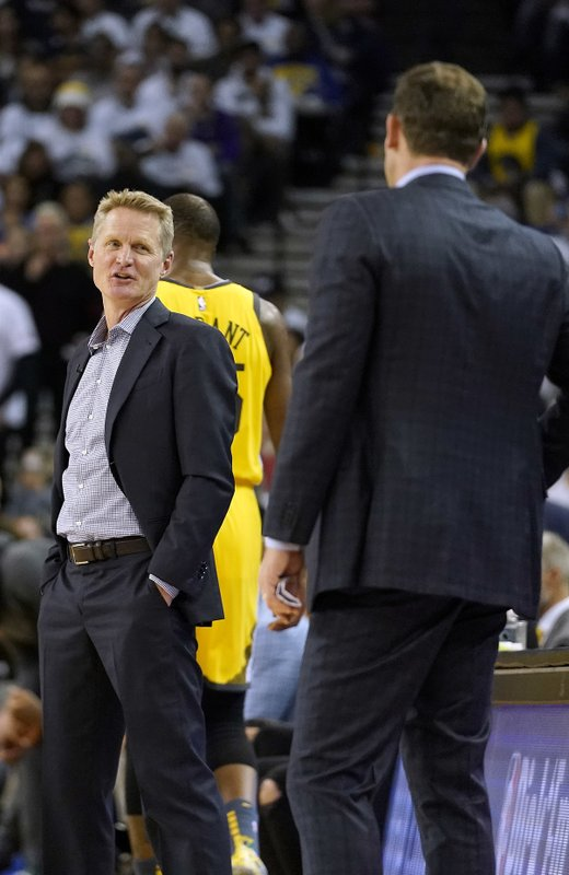 Golden State Warriors coach Steve Kerr, left, talks to Los Angeles Lakers coach Luke Walton during a timeout on the first half of an NBA basketball game Tuesday, Dec. (AP Photo/Tony Avelar)
