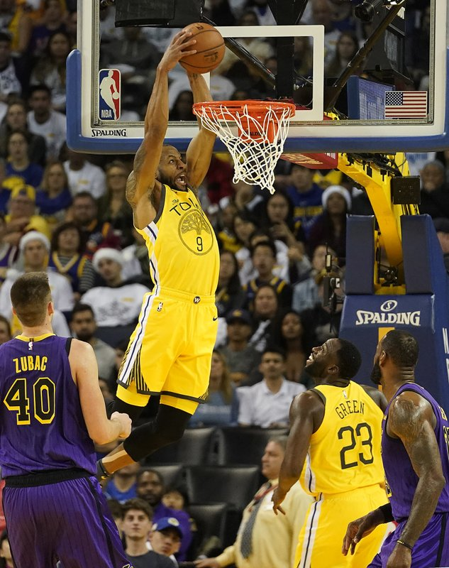 Golden State Warriors guard Andre Iguodala (9) dunks in front of Los Angeles Lakers center Ivica Zubac (40) during the first half of an NBA basketball game Tuesday, Dec. (AP Photo/Tony Avelar)