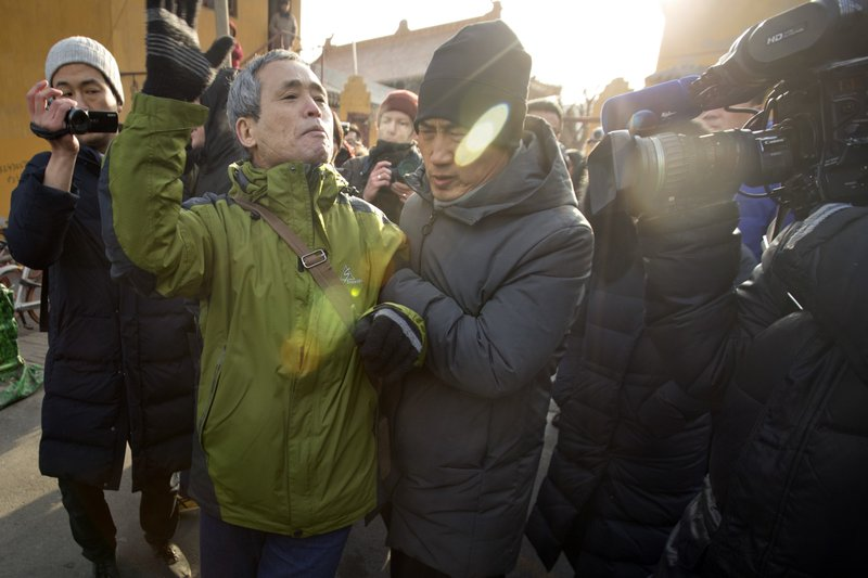 Plainclothes security officers take away a supporter of Chinese human rights lawyer Wang Quanzhang near the Secondary Intermediate People's Court of Tianjin northeastern China's Tianjin municipality, Wednesday, Dec. (AP Photo/Mark Schiefelbein)