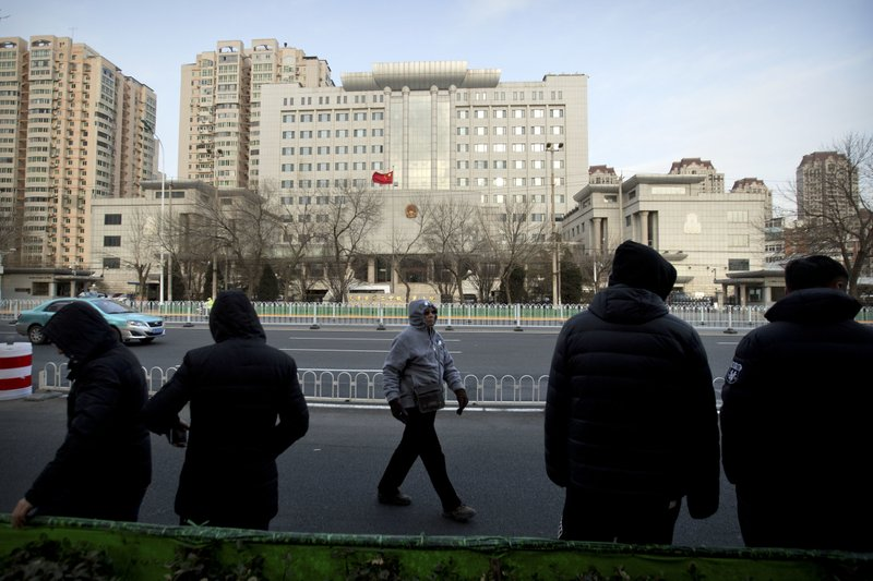 Plainclothes security officers stand in the street opposite the Secondary Intermediate People's Court of Tianjin northeastern China's Tianjin municipality, Wednesday, Dec. (AP Photo/Mark Schiefelbein)