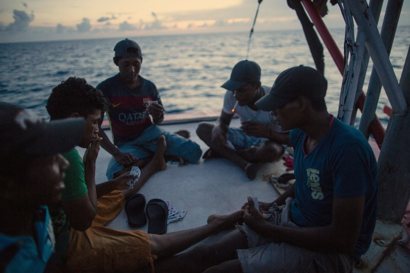 In this Sept. 10, 2018 photo, Miskito divers play a game of cards on a ship's stern as they are transported home after a two week fishing trip, near Savannah Cay, Honduras. (AP Photo/Rodrigo Abd)