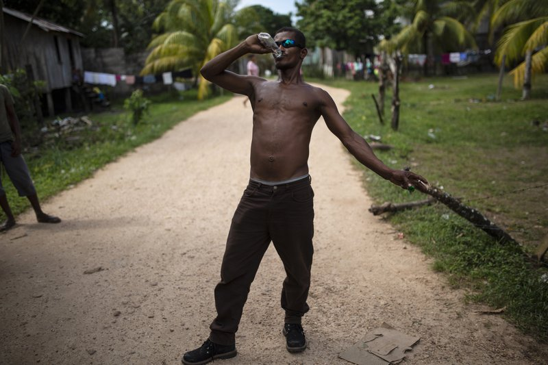 In this Feb 1, 2018 photo, Angel Ponce takes a swig of rum, in Puerto Lempira, Honduras. Among exotic, tropical vegetation along the Caribbean coast, the Mosquitia region is sprinkled with small fishing villages. (AP Photo/Rodrigo Abd)