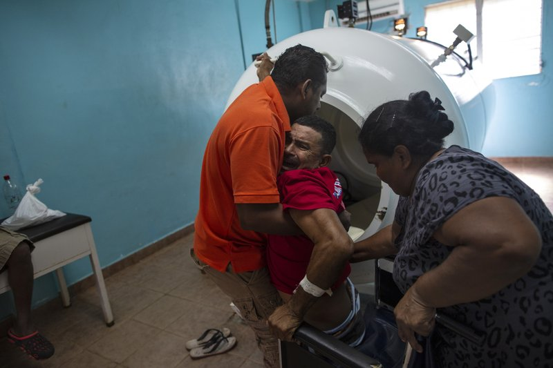 In this Feb. 9, 2018 photo, paralyzed by decompression sickness, lobster diver Misael Banegas Diaz, 49, is lifted by physical therapist Cedrak Waldan Mendoza into a hyperbaric chamber at the hospital in Puerto Lempira, Honduras. (back to diving) and they say it's because their kids are hungry.